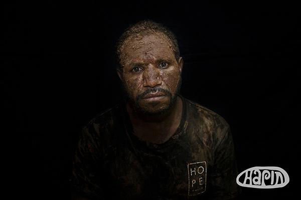 Yore (25) smeert zijn gezicht in met aarde als een teken van rouw.